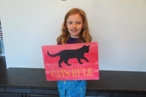 girl holding painted wood sign